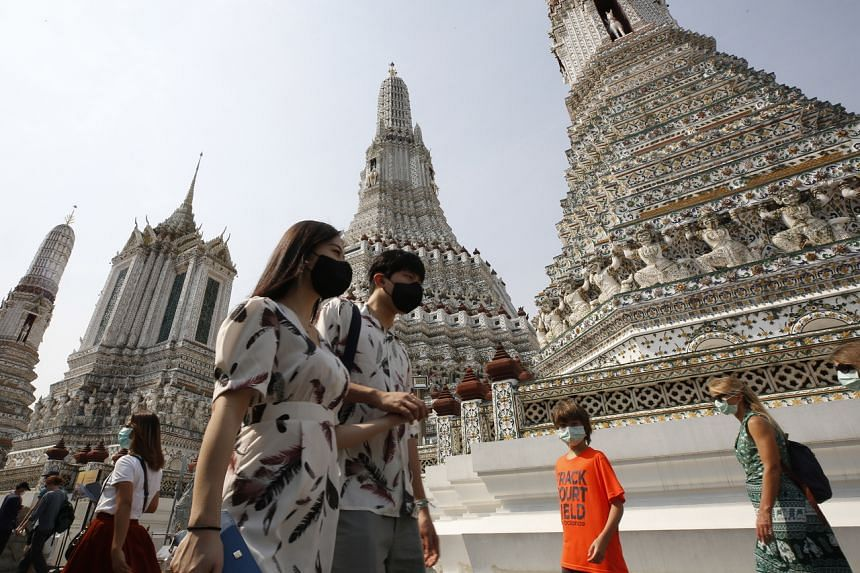 Tourists wear face masks at Wat Arun in Bangkok, on Jan 31, 2020.
