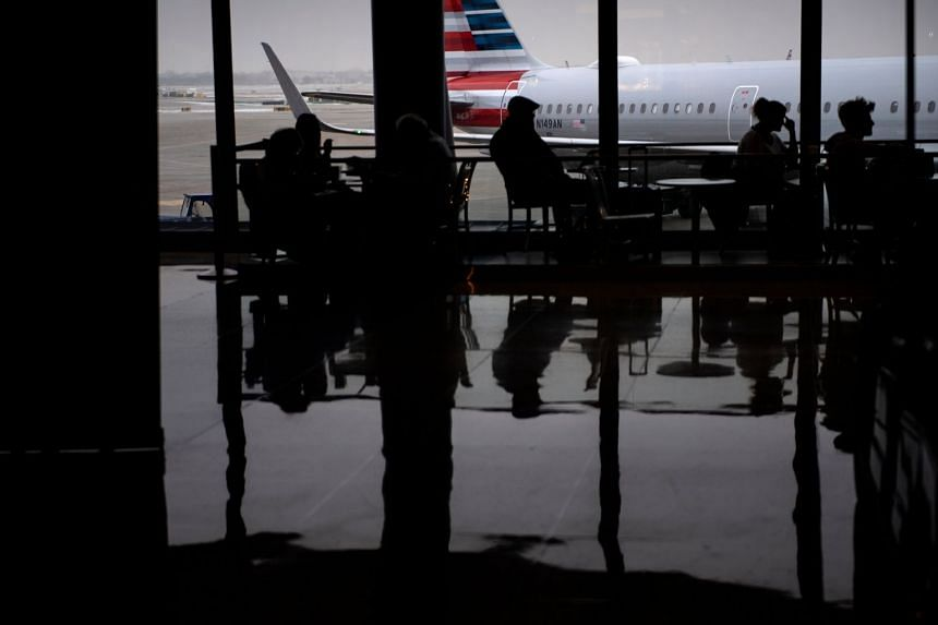 An American Airlines plane is seen as passengers wait at Chicago O'Hare International Airport in the US. The airline has announced flight cancellations but only from Feb 9 through March 27 and only its service from Los Angeles.