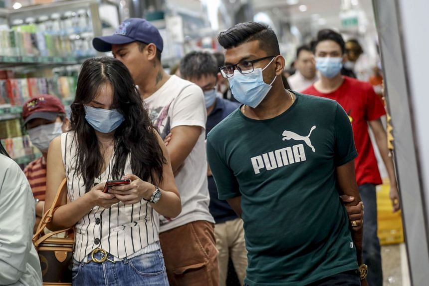 Customers wearing protective masks walk inside a shopping mall in Singapore, Jan 30, 2020.