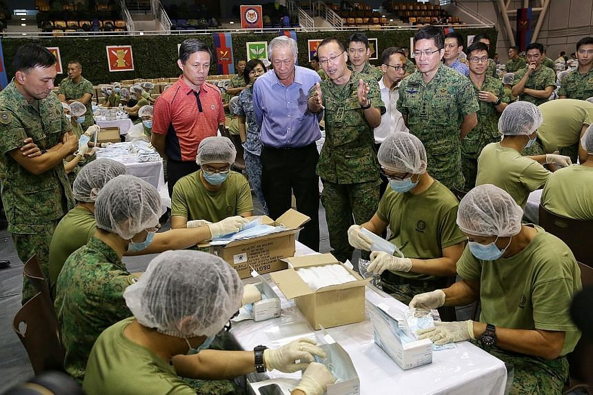 Above: Around 1,500 Singapore Armed Forces servicemen are working round the clock to ensure that the 5.2 million masks are packed in time. In the foreground are sealed boxes containing the packed masks. Left: Trade and Industry Minister Chan Chun Sin
