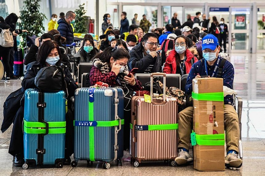 Passengers waiting to board a flight yesterday at Rome's Fiumicino airport, as a number of airlines halted or reduced flights to China in a bid to contain the spread of the Wuhan coronavirus. China sent two planes to Malaysia and Thailand yesterday t