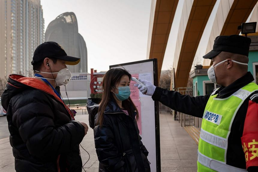 A security guard checks the temperature of a woman at the entrance to a park in Beijing on Jan 31, 2020.