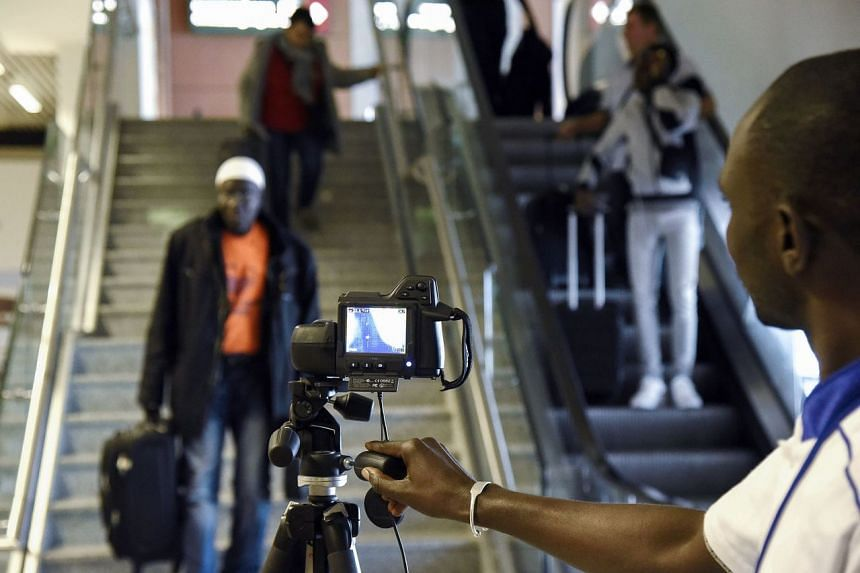 Health workers screen arriving passengers with a thermal scanner at the Blaise Diagne International Airport in Dakar, Senegal, on Jan 30, 2020.