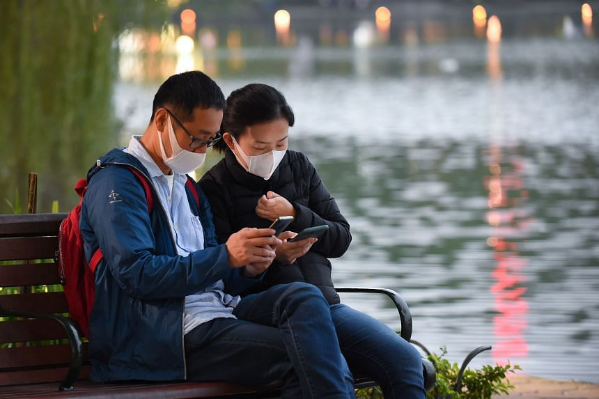 A couple wearing face masks using their mobile phones by the Hoan Kiem Lake in Hanoi, Vietnam, on Jan 31, 2020.