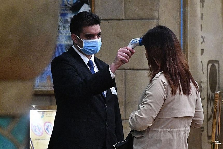 A woman entering the casino of the New Orient Landmark Hotel in Macau on Jan 22 getting her temperature checked.