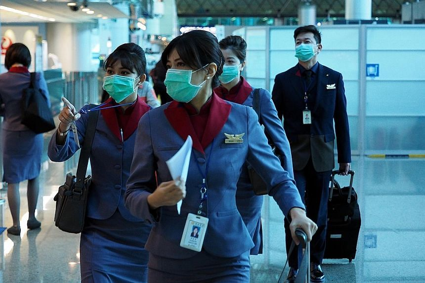 Flight attendants from Taiwan's China Airlines wearing protective masks at the Taoyuan International Airport in Taiwan last Thursday.