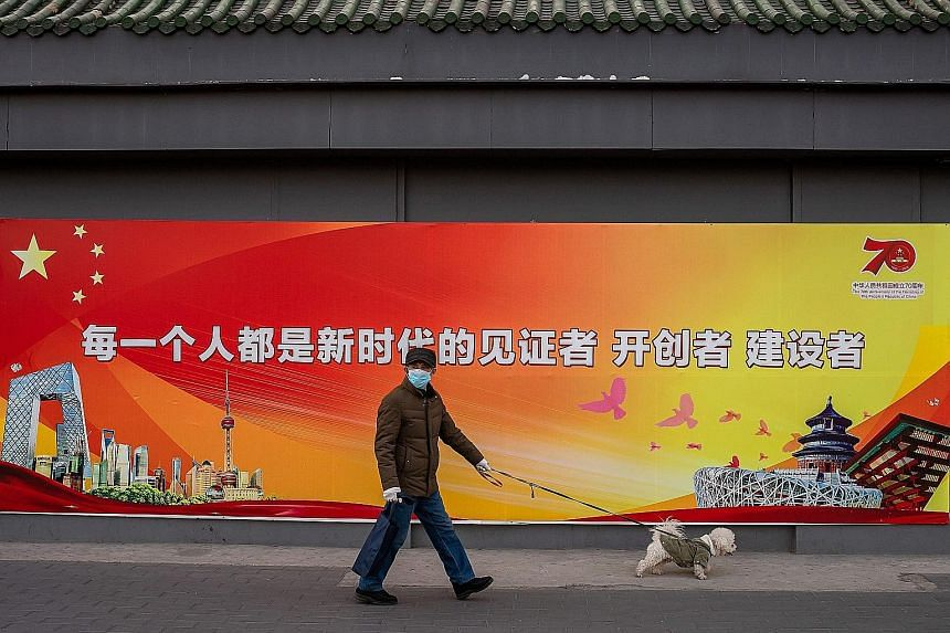"""A man wearing two protective masks and gloves walking his dog last Friday past a government propaganda poster in Beijing that reads """"Everyone is a witness of the new era""""."""