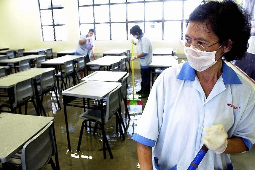 Cleaners disinfecting the floors of all the classrooms at Bowen Secondary School in an attempt to reduce the risk of infection during the Sars outbreak in Singapore, which lasted from March to July 2003.