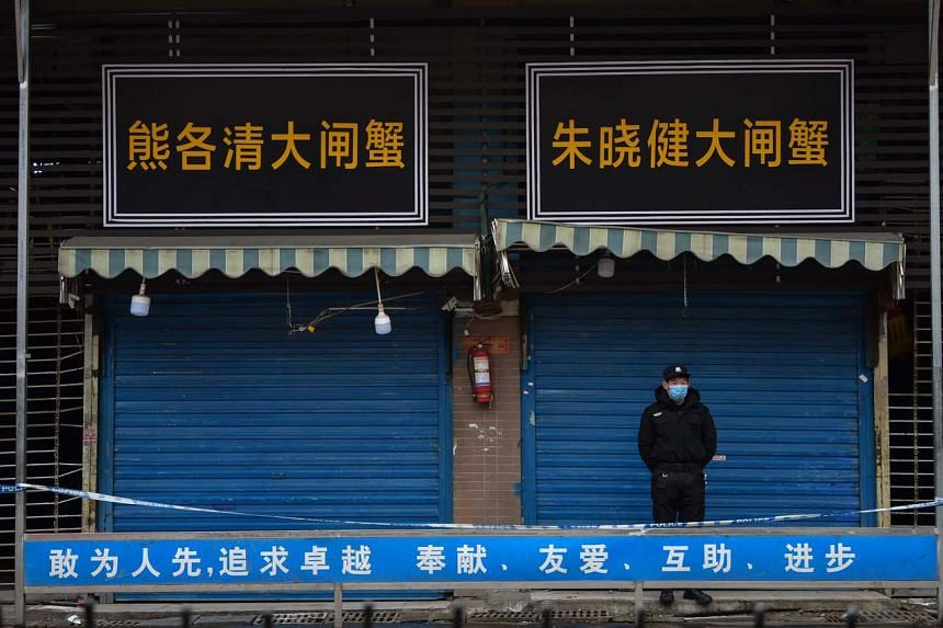 A security guard standing outside Huanan Seafood Wholesale Market where the coronavirus was detected in Wuhan, on Jan 24, 2020.