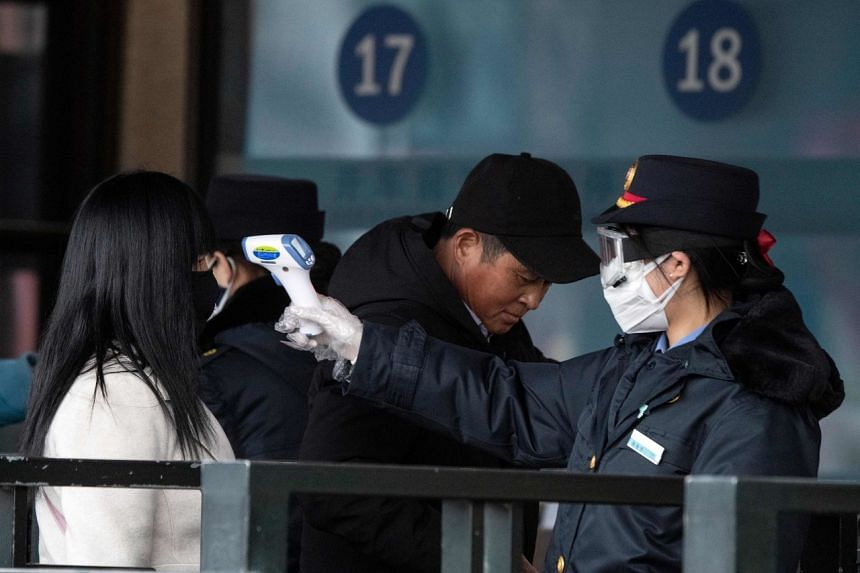 A security personnel checking the temperature of a passenger wearing a face mask at Beijing Railway Station, on Feb 1, 2020.