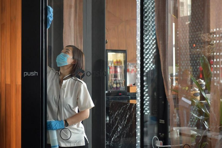A cleaner at Oasia Hotel Downtown sanitising the doors of the hotel's club lounge on Feb 2, 2020.