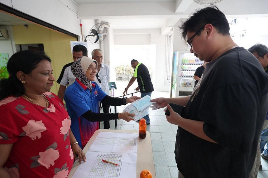 A resident collecting his masks at the collection counter at the Residents' Committee centre at Block 47 Telok Blangah Drive.