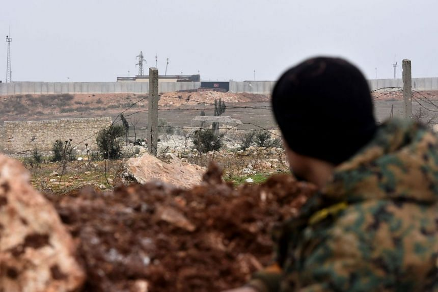 A Syrian army soldier looks at a Turkish military observation post in Aleppo's southwestern countryside during an ongoing pro-government offensive, on Jan 30, 2020.