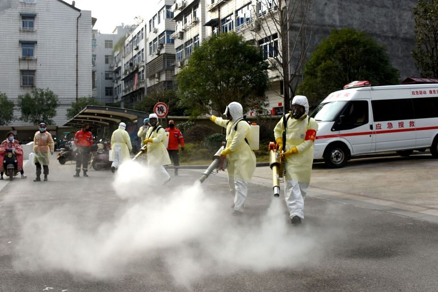 Volunteers in protective suits disinfect a residential compound in Zhejiang province, China, on Jan 30, 2020. Zhejiang has the highest number of coronavirus cases outside Hubei.