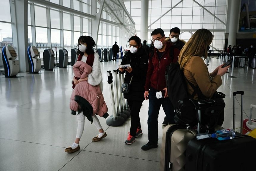 People are seen wearing masks at the John F. Kennedy Airport in New York City on Jan 31, 2020.