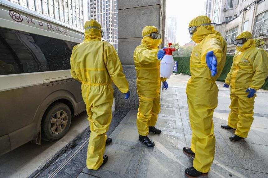 Staff members of a funeral parlour wearing protective suits disinfecting a colleague after transferring a body at a hospital in Wuhan, China, on Jan 30, 2020.