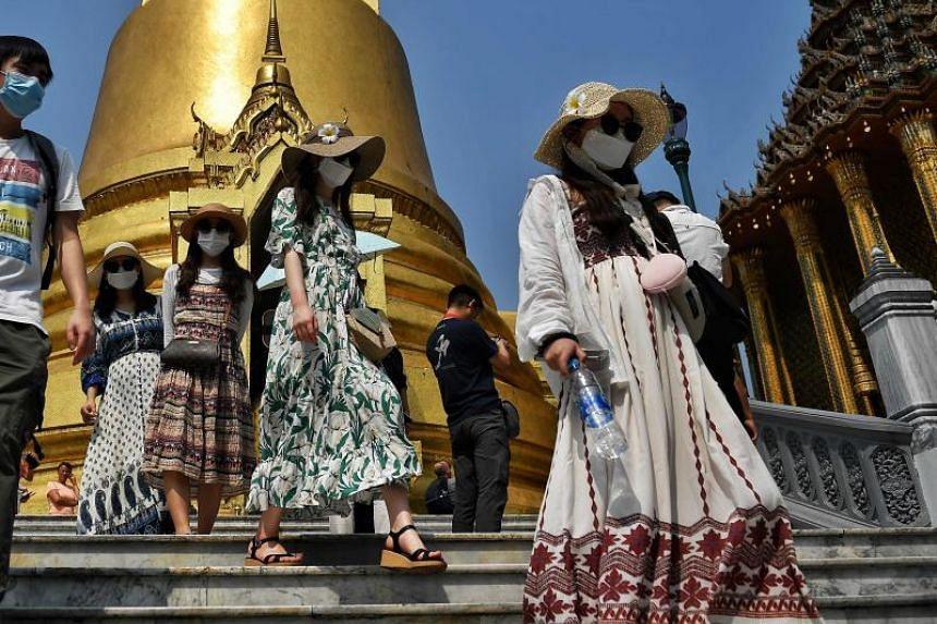 Tourists wearing face masks visit the Grand Palace in Bangkok on Jan 29, 2020.