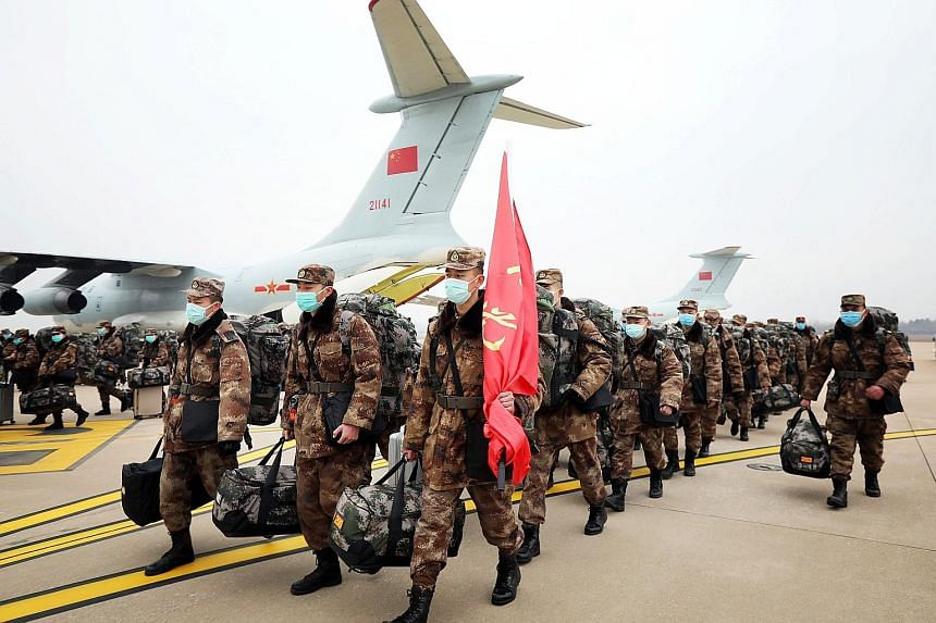 People's Liberation Army medical personnel arriving at Wuhan Tianhe International Airport yesterday. Some 1,400 military medics will be deployed at a new 1,000-bed hospital in Wuhan.