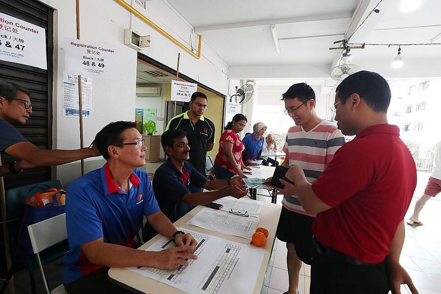 Social and Family Development Minister Desmond Lee (in red) visiting a mask collection counter manned by volunteers at the residents' committee centre at Block 47 Telok Blangah Drive yesterday. Distribution of the masks began on Saturday and will end