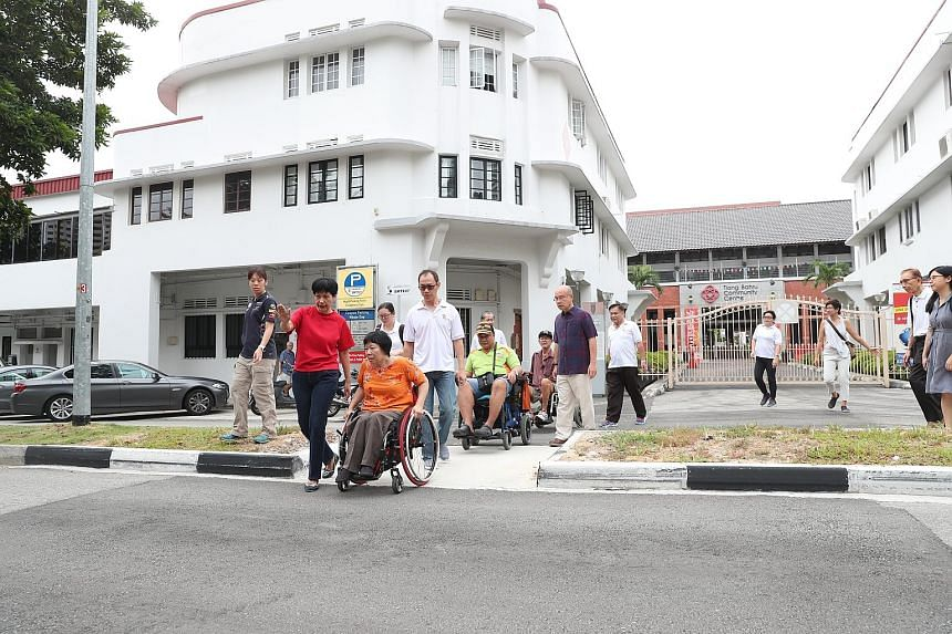Tanjong Pagar GRC grassroots adviser Indranee Rajah joining wheelchair users as they travelled on an enhanced barrier-free ramp in Tiong Bahru-Seng Poh estate yesterday. The changes were made in the area between SPD Ability Centre and Tiong Bahru Mar