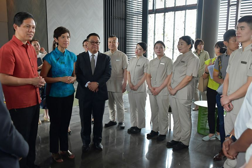 Trade and Industry Minister Chan Chun Sing (left), Manpower Minister Josephine Teo and Far East Hospitality chief executive Arthur Kiong with staff of Oasia Hotel Downtown yesterday. The ministers inspected precautionary measures at the hotel where a