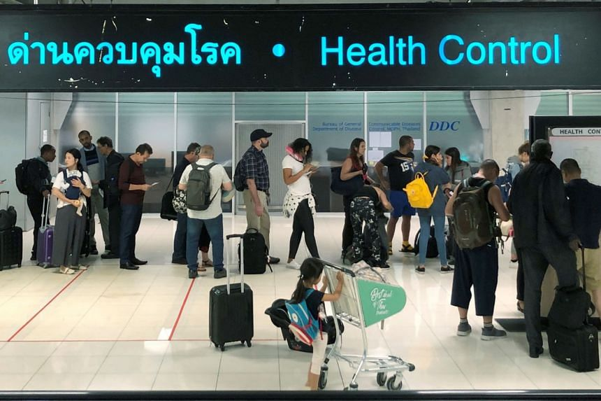 Tourists lining up in a health control area at the arrival section of the Suvarnabhumi international airport in Thailand on Jan 19, 2020.