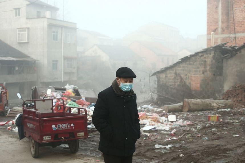 An elderly man wearing a mask walks in the village at sunrise in Jianli county, Hubei province, China, on Jan 28, 2020.