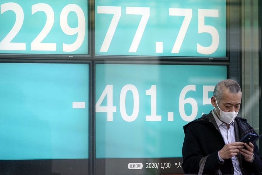 A man wearing a mask stands in front of a stock market indicator board in Tokyo, on Jan 30, 2020.