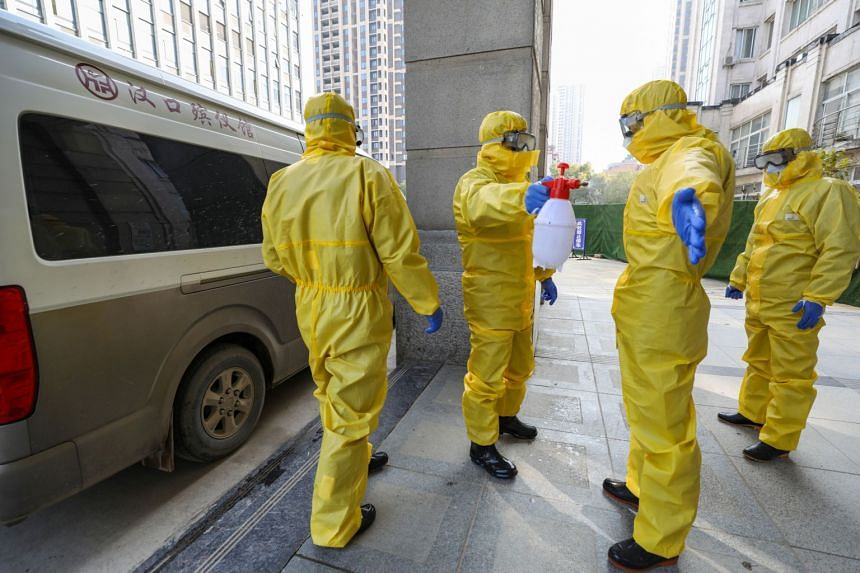 Funeral parlour staff in protective suits help a colleague with disinfection after they transferred a body at a hospital, following the outbreak of a new coronavirus in Wuhan, Hubei province, China, on Jan 30, 2020.