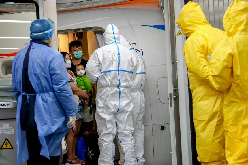 Workers in protective suits waiting for passengers from a Xiamen Airlines airplane as they get off the charter flight sent by the Chinese government to bring home Hubei residents from Bangkok, on Jan 31, 2020.