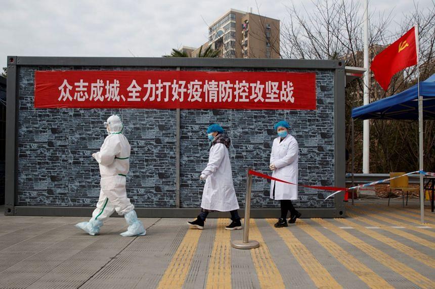 Hospital staff in protective garments walking to the Hubei province exclusion zone at the Jiujiang Yangtze River Bridge in Jiangxi province, China, on Feb 1, 2020.