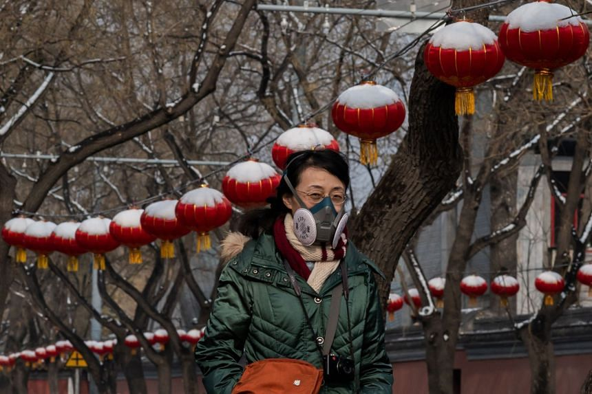 A woman wearing a protective mask to prevent the spread of the SARS-like virus walks on a streert after a snowfall in Beijing on Feb 2, 2020.