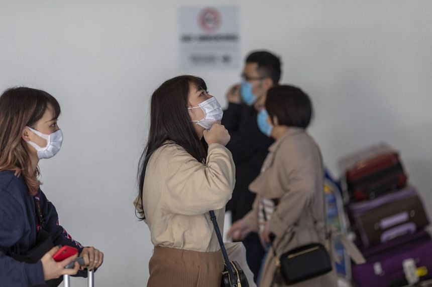 Travellers arrive at LAX Tom Bradley International Terminal wearing medical masks for protection against the novel coronavirus outbreak, on Feb 2, 2020, in Los Angeles, California.