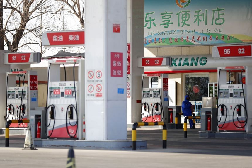 A petrol station staff member waits for customers at a petrol station in Beijing on Jan 29, 2020.