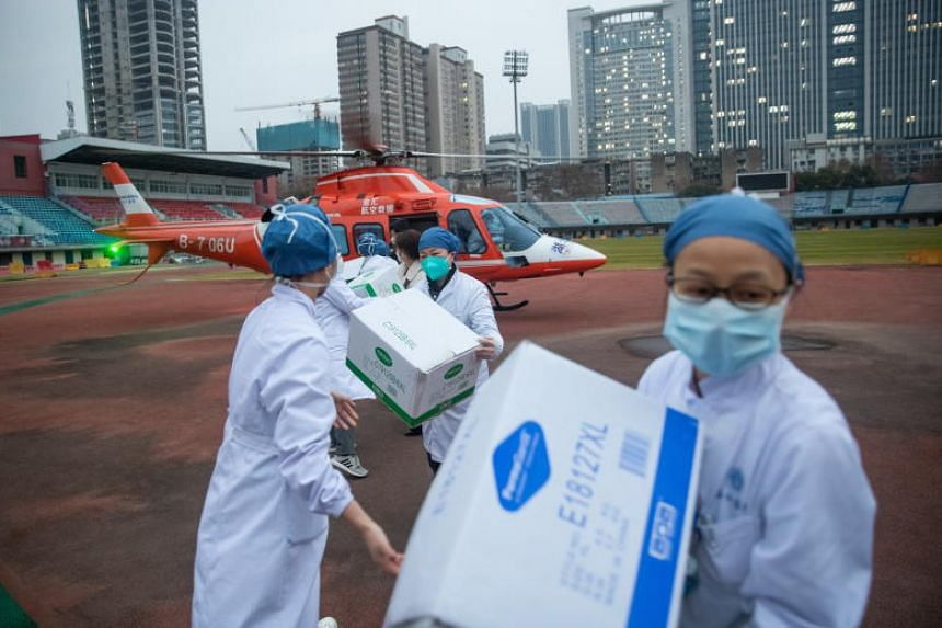 Medical staff of Concorde hospital offloading medical supplies from a helicopter in Wuhan, China, Feb 1, 2020.