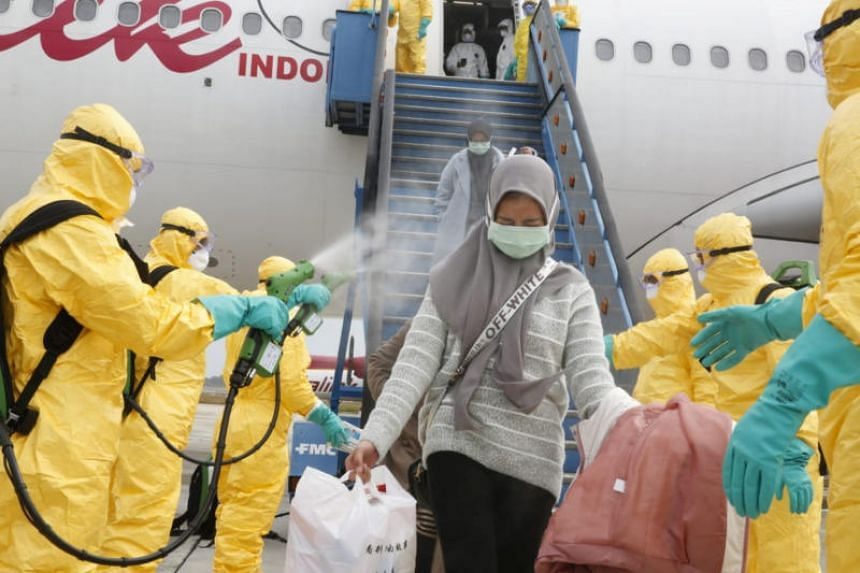 Medical officers spraying Indonesians with antiseptic on their arrival home from Wuhan, on Feb 2, 2020.
