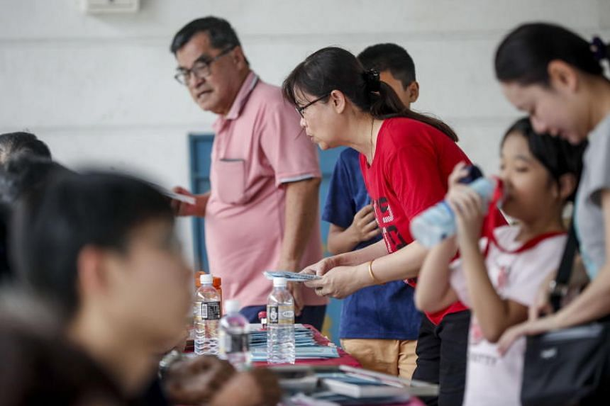 Residents collect surgical masks at a mask distribution point in Singapore, Feb 1, 2020.