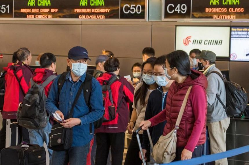 Chinese citizens wearing face masks check in to their Air China flight to Beijing, at Los Angeles International Airport, on Feb 2, 2020.