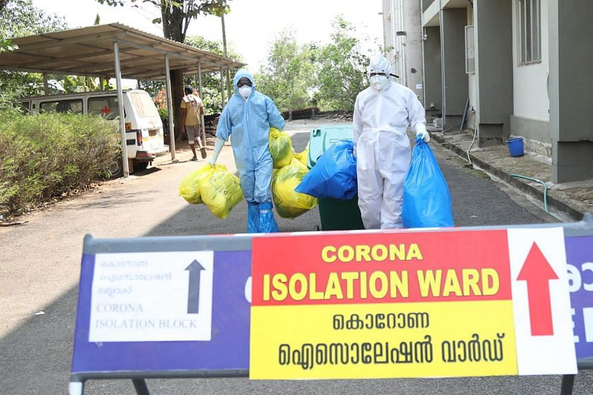 Medical staff in full protective suits carry medical waste as they exit from the coronavirus isolation ward in Kochi, Kerala, India, on Feb 3, 2020.