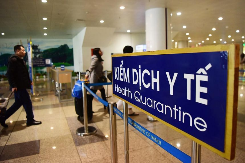 People walking past a health quarantine sign upon their arrival at Noi Bai international Airport in Hanoi on Jan 21, 2020.