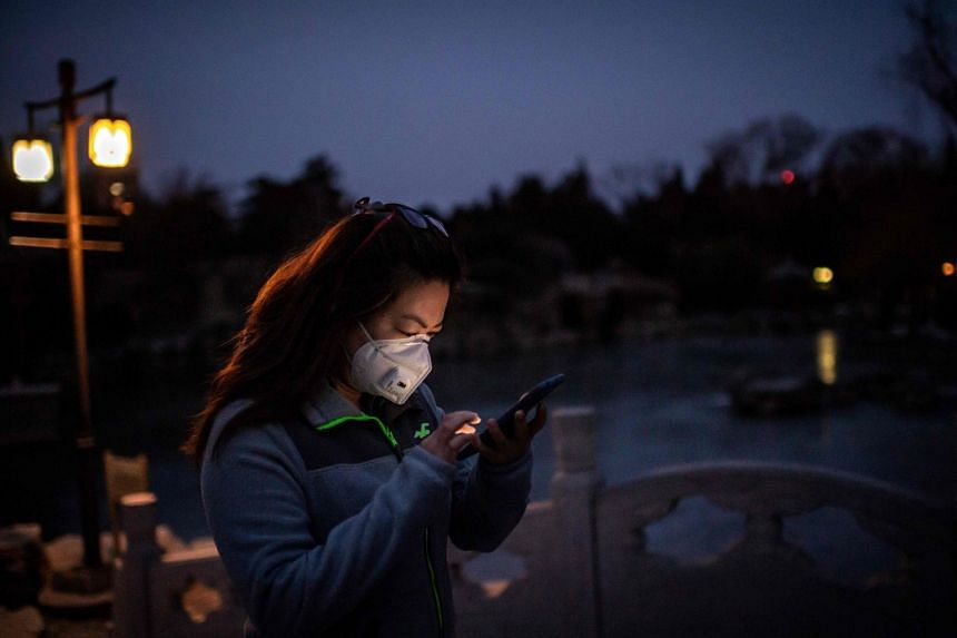 A woman wears a protective mask to prevent the spread of the coronavirus as she browses her smartphone while walking at a park in Beijing on Feb 1, 2020.