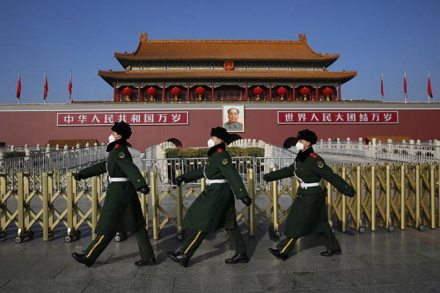 In a photo taken on Jan 31, 2020, Chinese paramilitary police officers in face masks patrol at Tiananmen Square in Beijing.