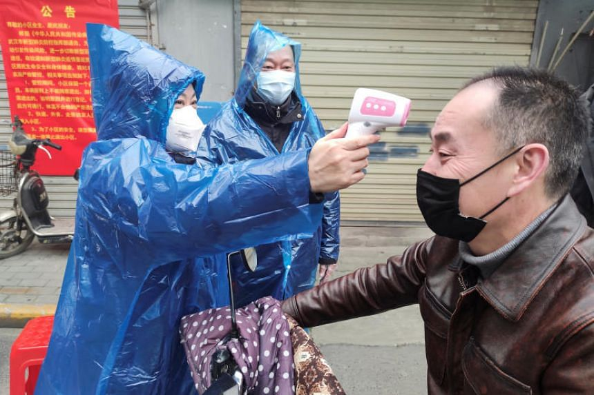 A worker takes the body temperature measurement of a man at the entrance to a residential compound following an outbreak of the new coronavirus in Wuhan, on Feb 1. 2020.