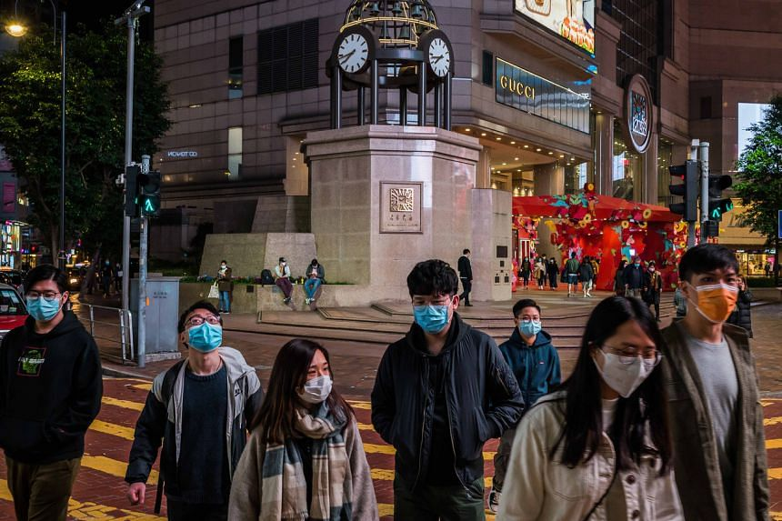 People wearing face masks in Hong Kong on Feb 3, 2020. The man, who had an underlying illness, developed muscle pain last week and came down with a fever.