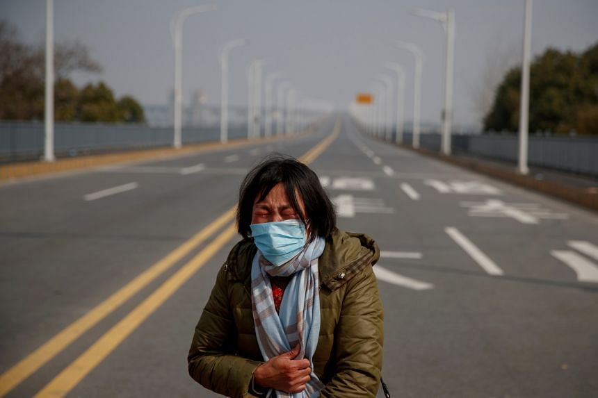 A mother pleads with police to allow her daughter to pass a checkpoint at the Jiujiang Yangtze River Bridge out of the Hubei province on Feb 1, 2020.