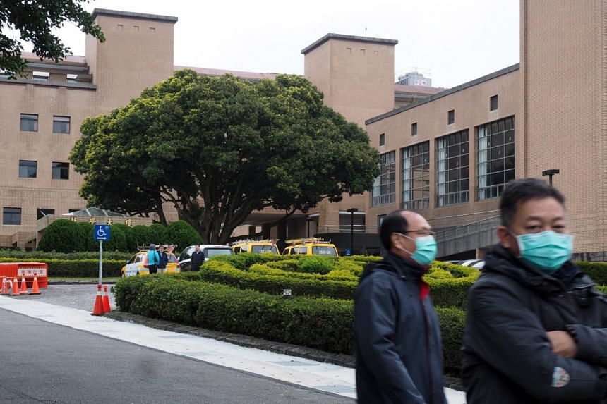 Two men walking past a building which will reportedly serve as a quarantine center for Taiwanese citizens evacuated from Wuhan; in Taipei, on Feb 3, 2020.