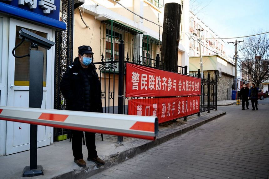 A security guard wearing a protective face mask stands guard at a compound with a banner reminding people to wear masks and wash hands in Beijing, on Feb 1, 2020.