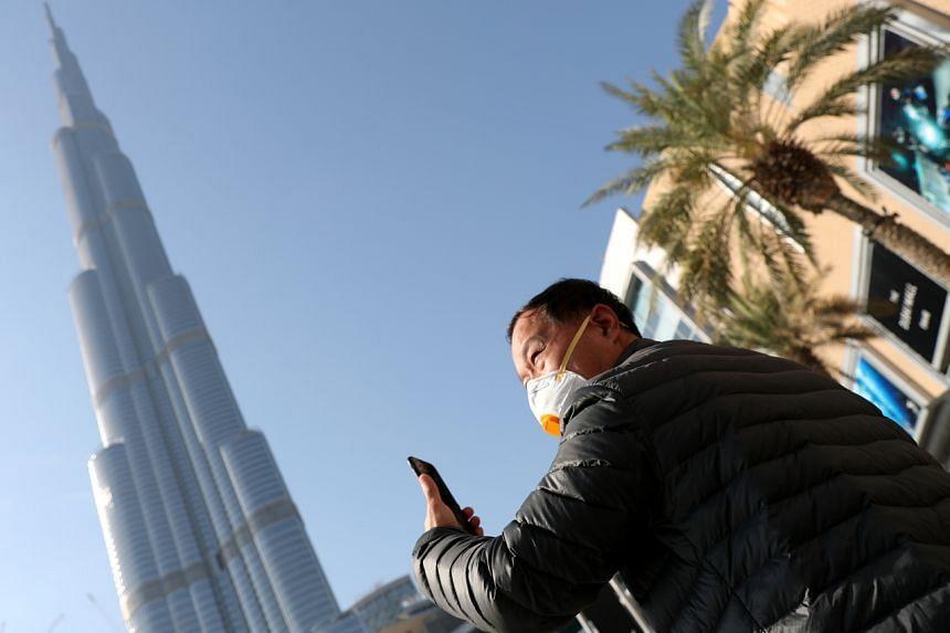 A man in a face mask taking a photo of the Burj Khalifa in Dubai, United Arab Emirates, on Feb 1, 2020.