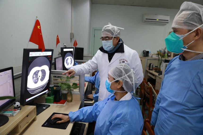 Medical workers inspect a CT scan image of a patient at the Zhongnan Hospital of Wuhan University in Wuhan, Hubei, China, on Feb 2, 2020.