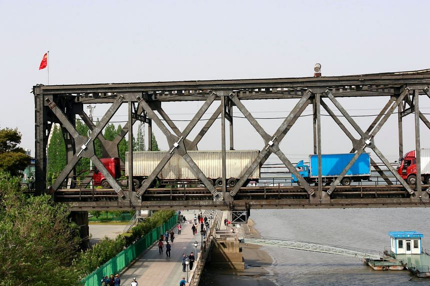 Trucks wait for border inspection at the Chinese end of the Friendship Bridge that connects Sinuiju, North Korea with Dandong, Liaoning province, China over the Yalu river on May 24, 2018.
